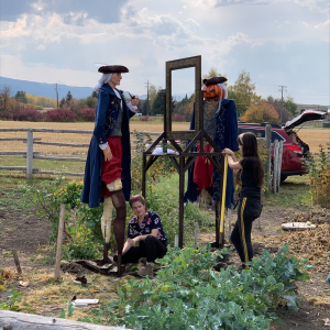 Two young women in a field of weeds install with shovels two large sculpture figures. The figure on the left is a figure of a man dressed in a blue coat from early American vintage and a three-cornered hat and has white hair tied back in a pony tail. He i