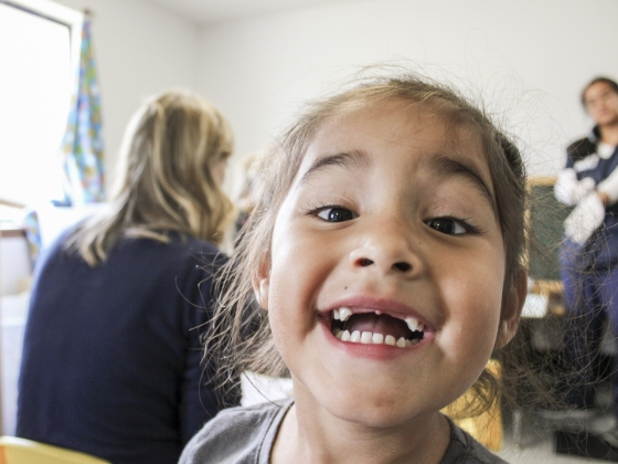 A child smiles for the camera showing her teeth. | Cooper McDonald for MSU