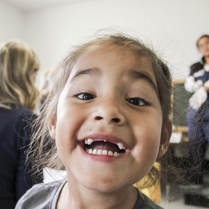 A child smiles for the camera showing her teeth.