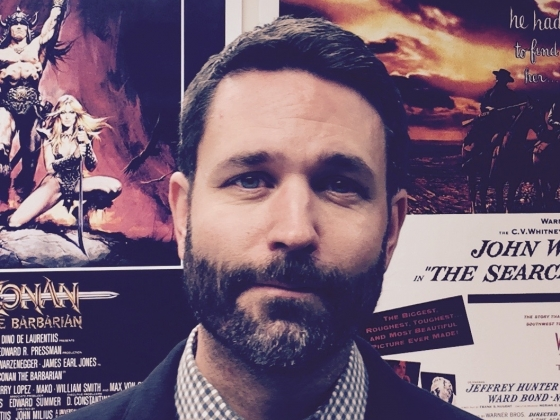 A photo of a man with brown hair and a close-cropped beard and mustache wearing a jacket and tie in front of film posters in the background. |