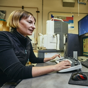 A woman sits at a desk with four computer monitors with images of bacteria.