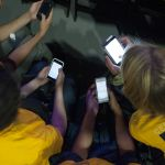 Students engage in some last-minute social media before the event.