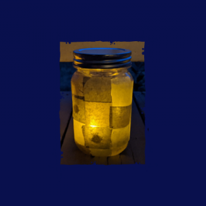 A golden lantern flickers on a porch in the dark evening light