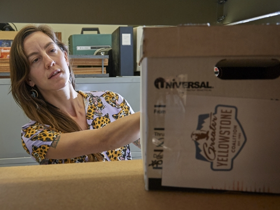 Photo of woman pulling a box of documents from a shelf in the library archive.   MSU photo by Kelly Gorham