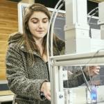 A student explains a machine during a design fair