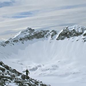 A skier surveys a possible run in the backcountry.