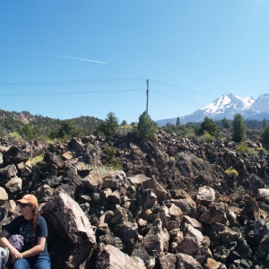 Photo of Rebecca on a blocky lava flow with Mount Shasta in the background