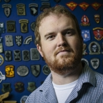 U.S. Navy veteran Sean Rogers poses for a portrait in front of a board of military patches.