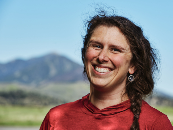 A close up portrait of a woman smiling towards the camera with blurred mountains in the background.   MSU Photo by Adrian Sanchez-Gonzalez