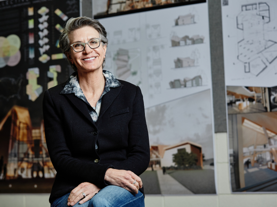 A woman in a black blazer and glasses sits for a portrait with design renderings in the background. | MSU Photo by Adrian Sanchez-Gonzalez