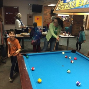 Students playing pool on a pool table.