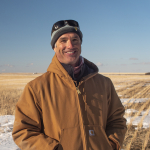 Photo of a man in a Carhart jacket and beanie in front of a field with snow and grain stubble and a clear blue sky.