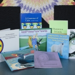 A collection of Native American children's books are laid out on a table