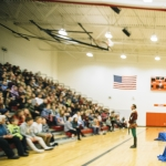 Actors perform a Shakespeare play in the gym of Chief Joseph Middle School in Bozeman before an audience of middle scholars who are sitting in the stands.