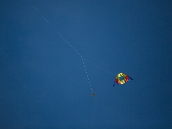Photo of a multi-colored kite flying in a blue sky. |