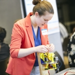 A woman adjusts gears on an engineering design project.