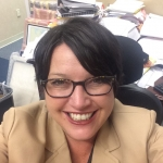 A selfie of a smiling woman with short dark hair, glasses and a tan jacket with office clutter in the background.