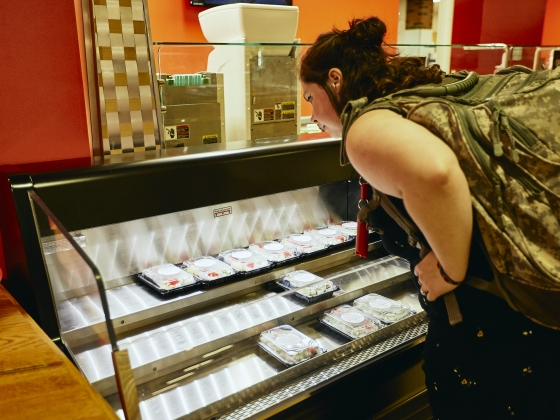A woman looks over an open air cooler with packaged sushi. | MSU Photo by Adrian Sanchez-Gonzalez