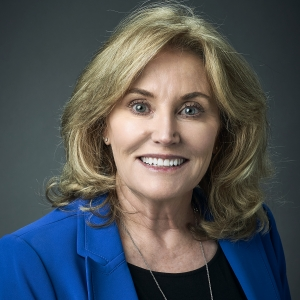 Head shot of a woman against a gray backdrop.