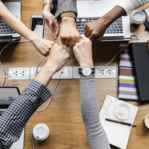 Co-workers hands above a table in a stacked in a show of team work.