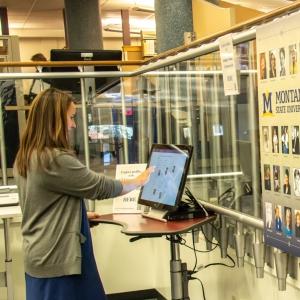 Photo of someone using the interactive Extraordinary Ordinary Women of MSU display