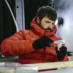 Kevin Hammonds, wearing orange down jacket, takes a snow sample in the Subzero Lab