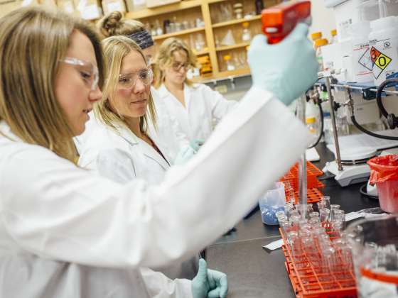 Women in lab jackets and safety glasses working with test tubes.   MSU photo by Adrian Sanchez-Gonzalez