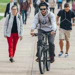A student rides a bicycle amongst a crowd through campus