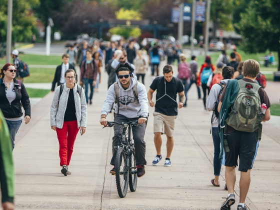 A student rides a bicycle amongst a crowd through campus | MSU Photo by Adrian Sanchez-Gonzalez