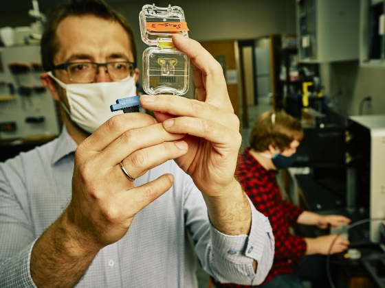 A man in a white face mask inspects a glass chip as a man works on a 3D printer in the background. | MSU Photo by Adrian Sanchez-Gonzalez