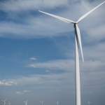 A group of wind turbines against a blue sky.