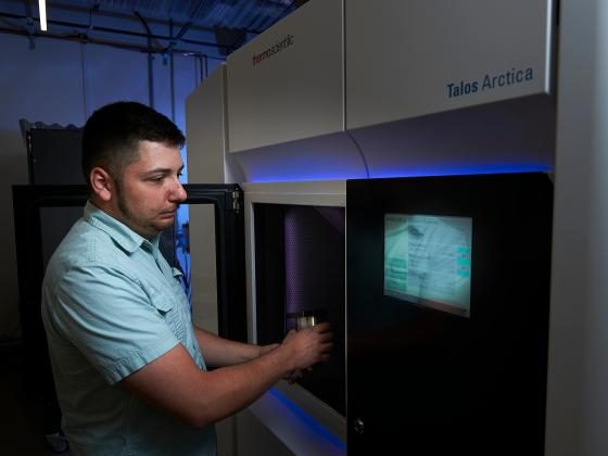 A man places a metal object in a large device with glowing monitors.   MSU photo by Kelly Gorham