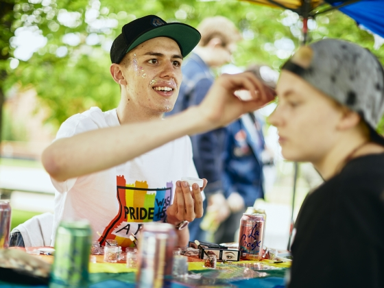 An artists paints a woman's face at a face painting booth   MSU Photo by Adrian Sanchez-Gonzalez