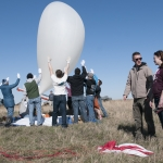 As volunteers guard a weather balloon being prepared for launch, Tim Basta and Micaela Moreni (at right) discuss the payload train in front of them. Basta will graduate from MSU in May, and Moreni will take over some of his responsibilities in the BOREALIS program. (MSU photo by Evelyn Boswell).
