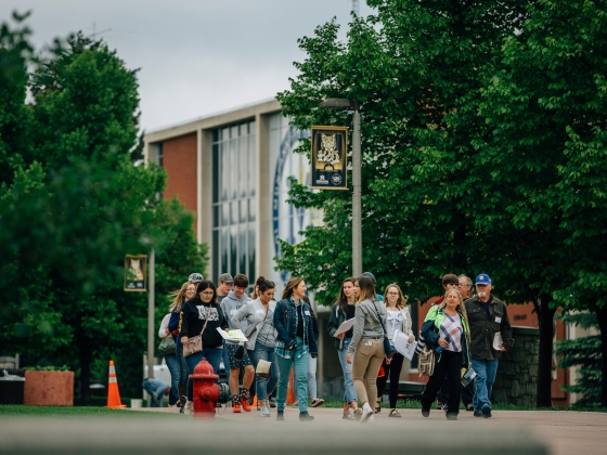 Students and family members tour the Montana State University campus on a spring day. MSU's Renne Library provides the background behind the group.