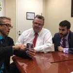 Michael Fox, left, demonstrates the DugalDiabetes mobile app to Montana Sen. Jon Tester, center, and legislative assistant Justin Folsom. Photo courtesy of Diane Smith.