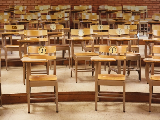 """Chairs in an empty classroom with stickers on them that read, """"Do not sit here."""" 