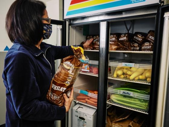 A woman in a blue sweatshirt stocks loaves of bread into a refrigerator. | MSU Photo by Adrian Sanchez-Gonzalez