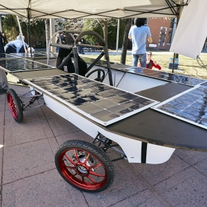A solar-powered car is displayed under a canopy