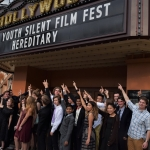 Group of student filmmakers pictured underneath International Youth Silent Film Festival banner.