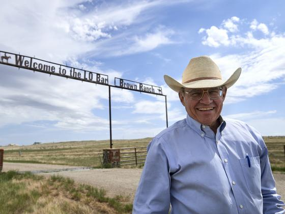 Man in a cowboy hat posing in front of a gate to a ranch | MSU photo by Kelly Gorham