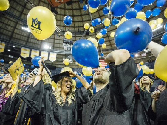 People wearing black caps and gowns celebrating as blue and gold balloons fall around them. | MSU photo by Adrian Sanchez-Gonzalez