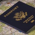 Photo of passport and travel paraphernalia.