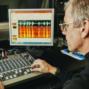 Rob Maher works a sound mixing board with computer monitor displaying wave forms
