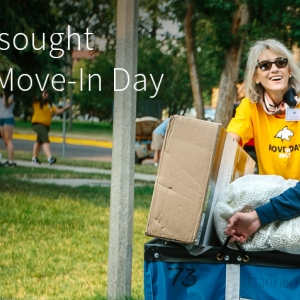 An incoming female student and an MSU volunteer push a cart full of belongings along a sidewalk on Move-In Day in this file photo.