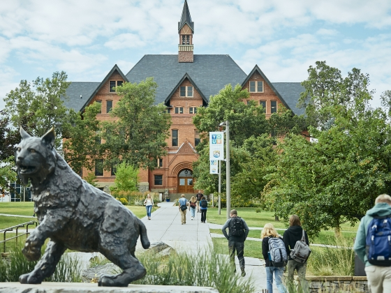 A landscape view of Montana Hall with a statue of a bobcat in the foreground. | MSU Photo by Adrian Sanchez-Gonzalez
