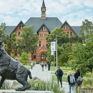 A landscape view of Montana Hall with a statue of a bobcat in the foreground.
