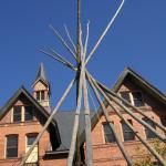 A tipi made of wood stands in front of a older red brick building characterized by two peaked gabled and a prominent black topped brick cupola against a wash of brilliant blue sky.