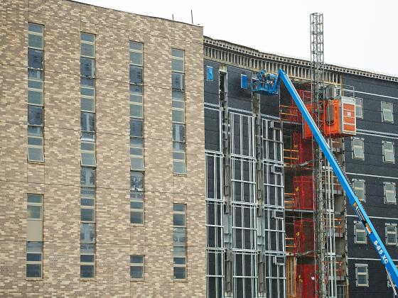 Wide photo of a large building under construction with construction workers in a lift. | MSU photo by Kelly Gorham