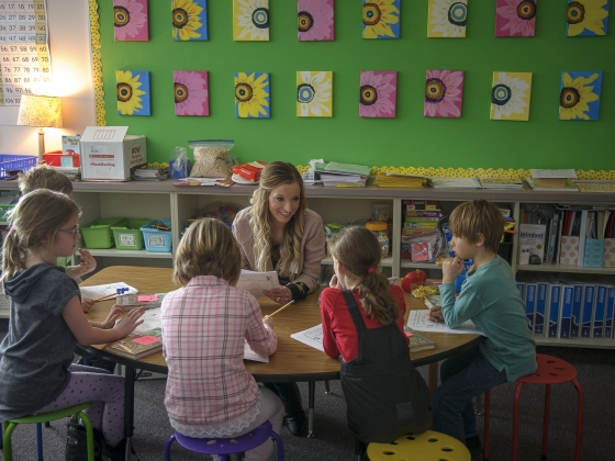 A woman reads an assignment sheet surrounded by second-graders in a classroom. | MSU Photo by Kelly Gorham